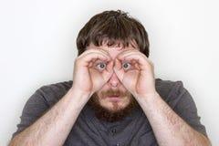 hombre que intenta espiar Imagen de archivo libre de regalías