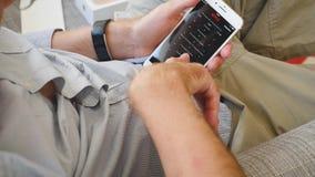 Hombre que intenta la película más app del reloj del app Netflix del iPhone 8 más finales de almacen de metraje de vídeo