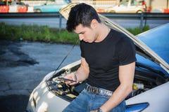 Hombre que intenta reparar el coche y la ayuda que busca en el teléfono Fotografía de archivo libre de regalías
