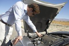 Hombre que intenta reparar su coche Imágenes de archivo libres de regalías