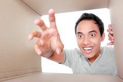Hombre que intenta tomar a algo la caja del interior Imagenes de archivo
