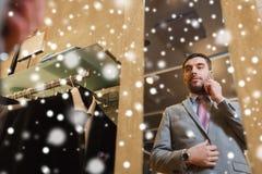 Hombre que invita a smartphone en el espejo de la tienda de ropa Imagen de archivo libre de regalías
