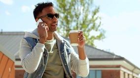 Hombre que invita a smartphone y que bebe el café metrajes
