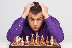 Hombre que juega a ajedrez en el fondo blanco Foto de archivo libre de regalías