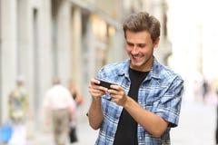 Hombre que juega al juego con un teléfono elegante Fotos de archivo
