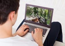 Hombre que juega al juego de acción en el ordenador portátil en casa Fotografía de archivo