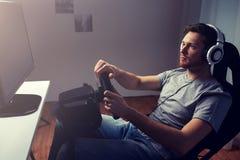 Hombre que juega al videojuego de las carreras de coches en casa Fotografía de archivo