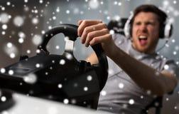 Hombre que juega al videojuego de las carreras de coches con la rueda Fotografía de archivo
