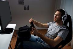 Hombre que juega al videojuego de las carreras de coches en casa Foto de archivo