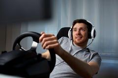 Hombre que juega al videojuego de las carreras de coches en casa Imágenes de archivo libres de regalías