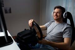 Hombre que juega al videojuego de las carreras de coches en casa Fotos de archivo libres de regalías