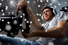 Hombre que juega al videojuego de las carreras de coches en casa Fotografía de archivo libre de regalías