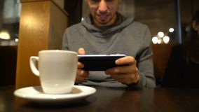Hombre que juega al videojuego en el café, ganando mostrando el gesto del sí, apego del artilugio metrajes