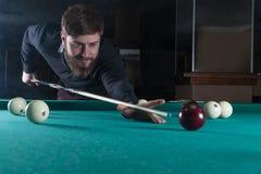 Hombre que juega billares mirada en la bola imagenes de archivo