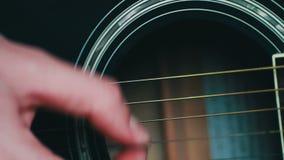 Hombre que juega cierre de la guitarra acústica para arriba almacen de metraje de vídeo