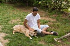 Hombre que juega con el perro fotografía de archivo