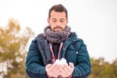 Hombre que juega con la nieve snowball Fotos de archivo