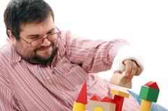 Hombre que juega con los ladrillos del juguete imagen de archivo