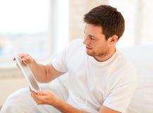 Hombre que juega con PC de la tableta en casa Fotos de archivo libres de regalías