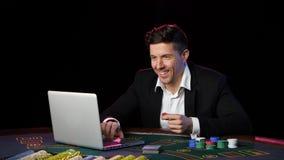 Hombre que juega el póker en línea en una tabla Cierre para arriba almacen de metraje de vídeo