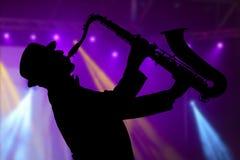 Hombre que juega en el saxofón contra la perspectiva de lig hermoso Fotografía de archivo