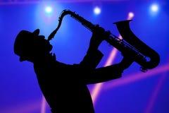 Hombre que juega en el saxofón contra la perspectiva de lig hermoso Foto de archivo