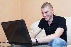 Hombre que juega en juegos en la computadora portátil Imagen de archivo libre de regalías