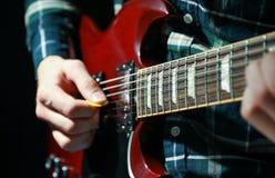 Hombre que juega en la guitarra eléctrica contra fondo oscuro imagen de archivo