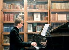 Hombre que juega en piano de cola negro Imagen de archivo libre de regalías