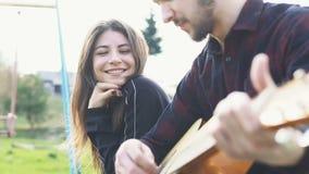 Hombre que juega en una guitarra al aire libre Jugar música en una guitarra acústica almacen de video