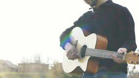 Hombre que juega en una guitarra al aire libre Jugar música en una guitarra acústica metrajes