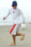Hombre que juega a fútbol de la playa Imagen de archivo libre de regalías