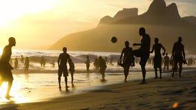 Hombre que juega a fútbol en la playa en el Brasil metrajes