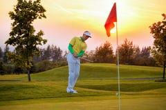 Hombre que juega a golf contra puesta del sol Imagenes de archivo