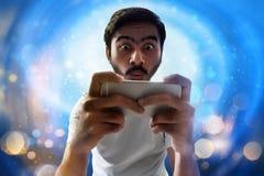 Hombre que juega a juegos móviles en fondo del bokeh foto de archivo libre de regalías