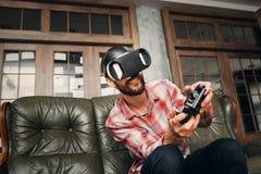 Hombre que juega a los videojuegos en auriculares de la realidad virtual Foto de archivo