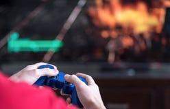 Hombre que juega a los videojuegos que soplan la materia para arriba Fotografía de archivo