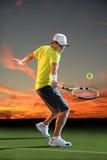 Hombre que juega a tenis en la puesta del sol imagen de archivo libre de regalías