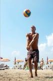 Hombre que juega a voleibol en una playa. Fotografía de archivo libre de regalías