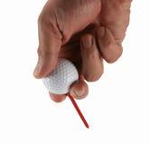 Hombre que junta con te una pelota de golf Foto de archivo libre de regalías