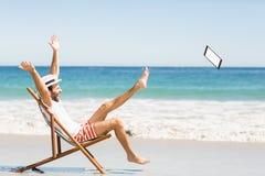 Hombre que lanza la tableta digital en la playa Fotos de archivo