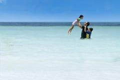 Hombre que lanza a su hija en la playa foto de archivo