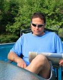 Hombre que lee cerca de una piscina Imágenes de archivo libres de regalías