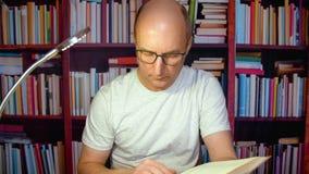 Hombre que lee la enciclopedia interesante en la biblioteca científica, fondo del estante para libros almacen de video