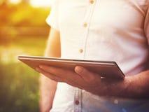 Hombre que lee la tableta digital al aire libre Imagen de archivo