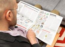 Hombre que lee los pioliticians de Charlie Hebdo como setas Imagenes de archivo
