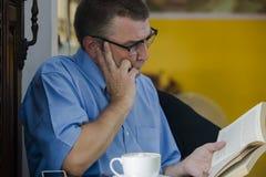Hombre que lee seriamente fotos de archivo