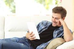 Hombre que lee un ebook o una tableta en casa Foto de archivo