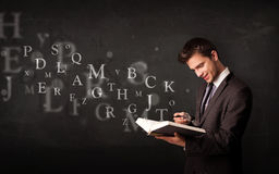Hombre que lee un libro con las letras del alfabeto Imágenes de archivo libres de regalías