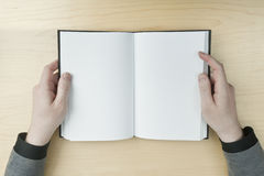 Hombre que lee un libro en blanco Foto de archivo